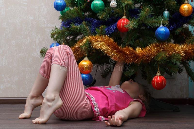 Liten flicka som tillbaka ligger på henne under julgranen royaltyfri bild