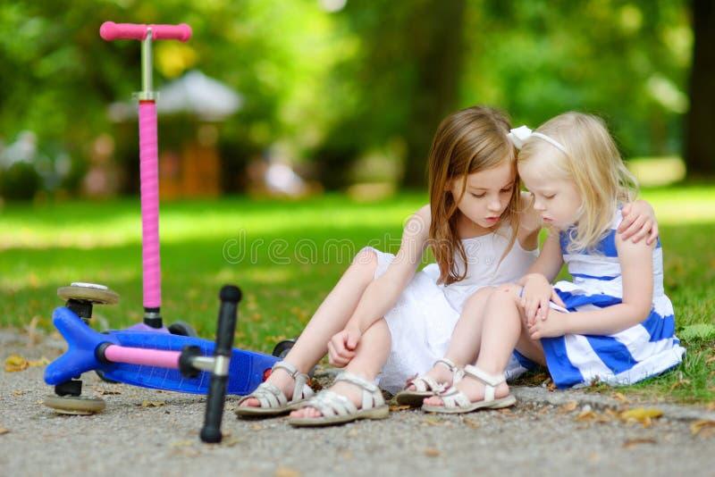 Liten flicka som tröstar hennes syster efter olycka royaltyfria bilder