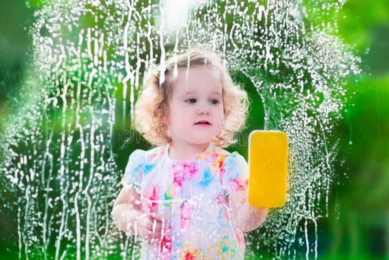 Liten flicka som tvättar ett fönster arkivfoton