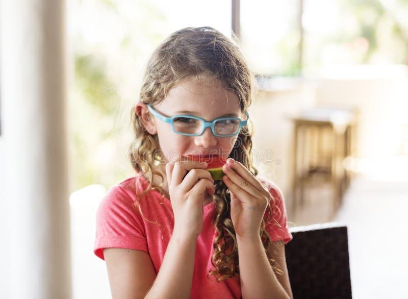 Liten flicka som tycker om äta vattenmelon royaltyfri fotografi