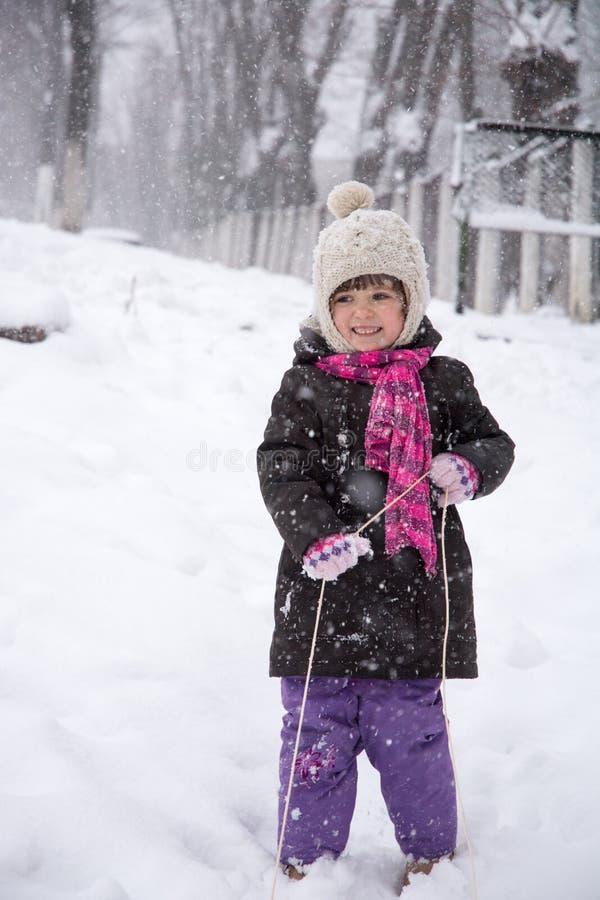 Liten flicka som tycker om en släderitt Sledding för barn Barnlek utomhus i snö royaltyfri foto