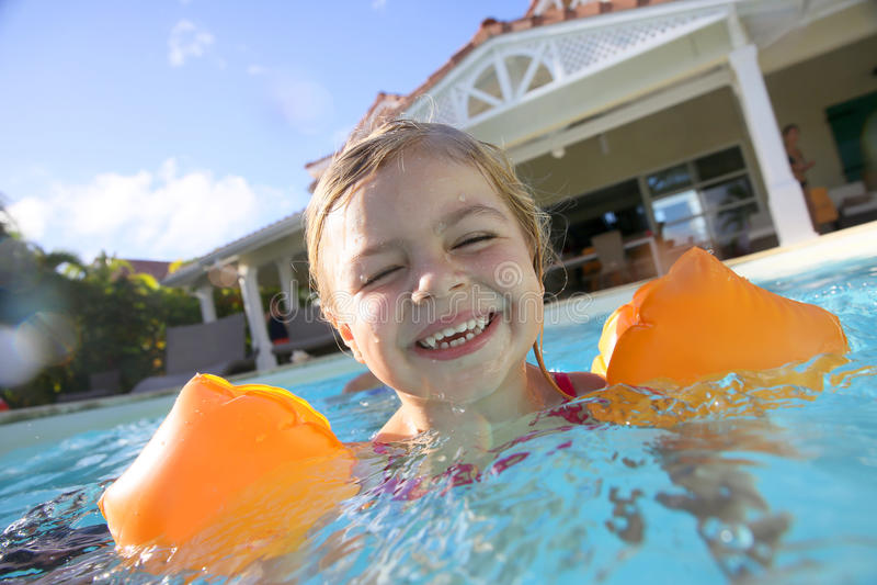 Liten flicka som tycker om simbassängen fotografering för bildbyråer
