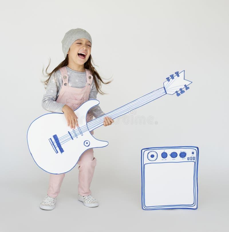 Liten flicka som tycker om spela gitarren fotografering för bildbyråer
