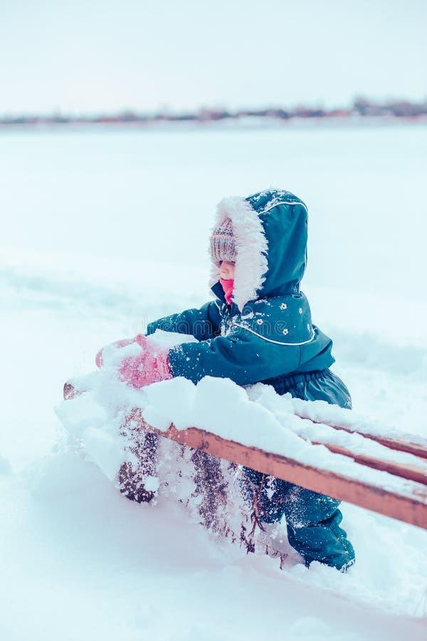 Liten flicka som tycker om vintern som tar bort sn? fr?n en b?nk fotografering för bildbyråer