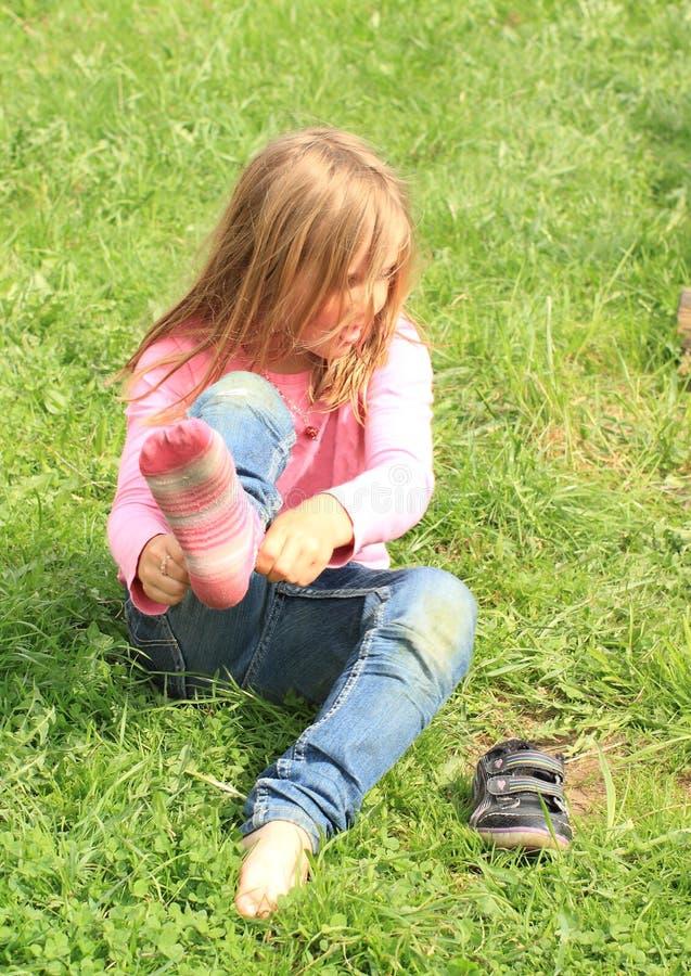 Liten flicka som upp klär sockor royaltyfria bilder