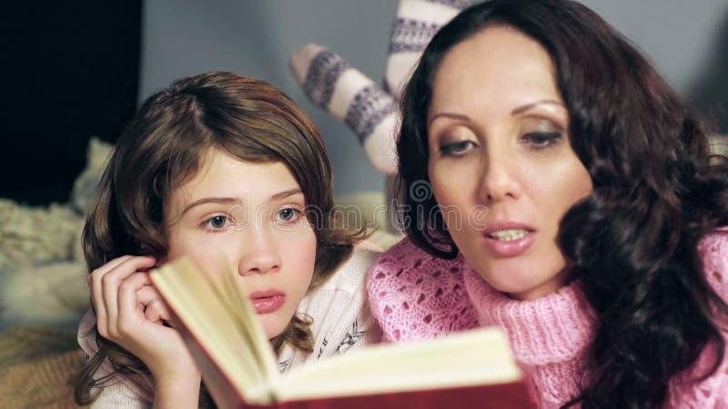 Liten flicka som uppmärksamt lyssnar till sagor som läser med modern, slut upp royaltyfria foton