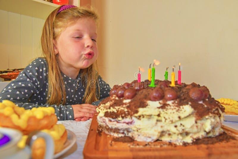 Liten flicka som ut blåser stearinljus på hennes födelsedagkaka Liten flicka som firar hennes sex födelsedag Födelsedagkaka och l arkivfoto