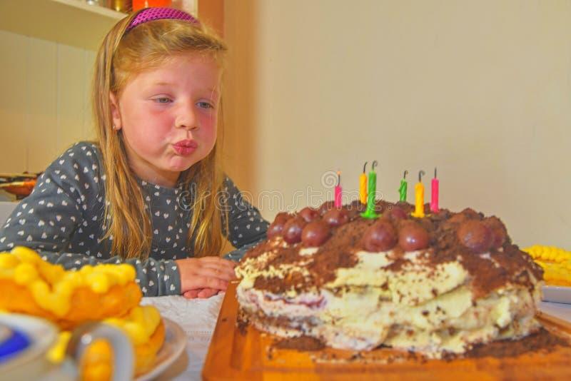 Liten flicka som ut blåser stearinljus på hennes födelsedagkaka Liten flicka som firar hennes sex födelsedag Födelsedagkaka och l royaltyfri foto
