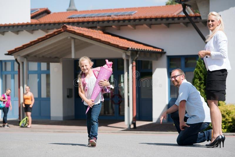 Liten flicka som ut får - av - skola efter hennes första dag arkivbild