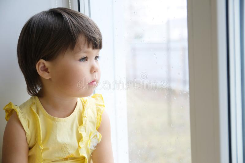 Liten flicka som ut ser fönstret som längtar efter något solsken barnsammanträdehem på den regniga dagen royaltyfri fotografi