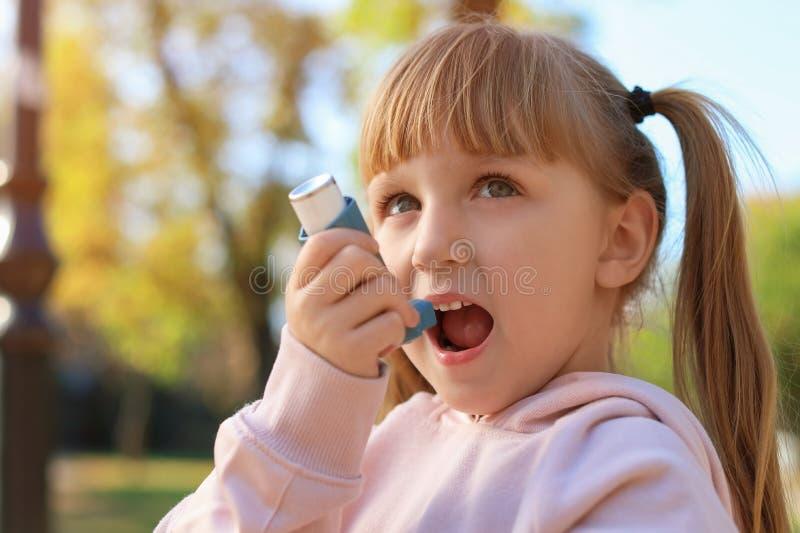 Liten flicka som utomhus använder astmainhalatorn arkivfoto