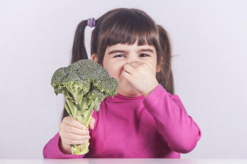 Liten flicka som vägrar att äta hennes grönsaker arkivfoton