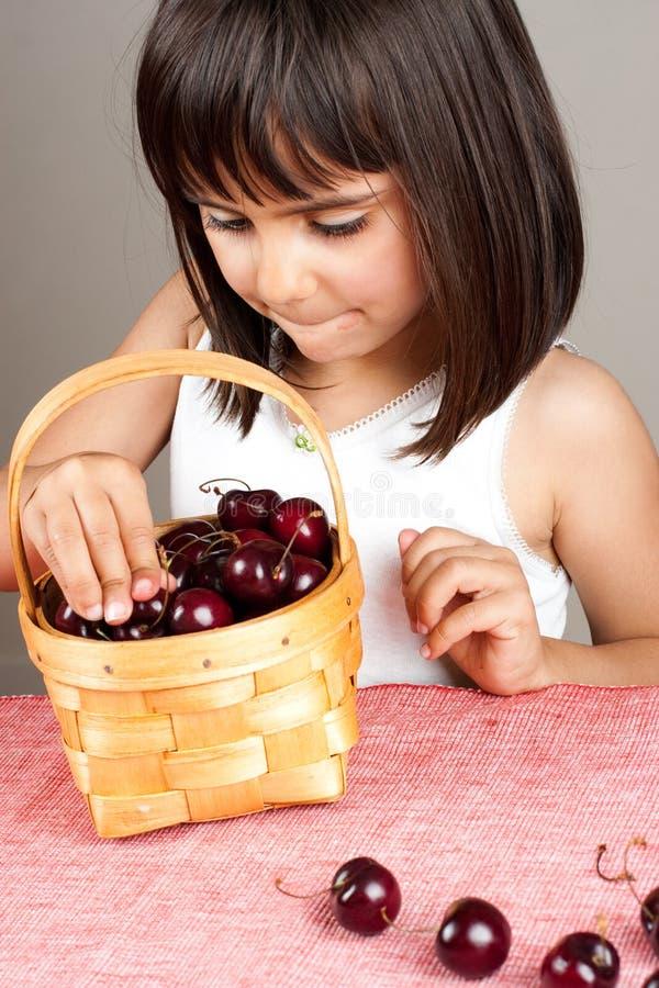 Liten flicka som väljer körsbär från en korg royaltyfri foto