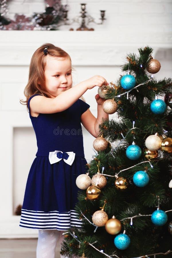 Liten flicka som väntar på ett mirakel i julpynt _ royaltyfri fotografi