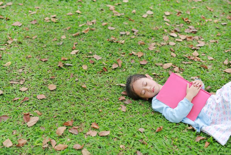 Liten flicka som vilar med boken som ligger på grönt gräs med torkade sidor i sommarträdgården royaltyfri bild