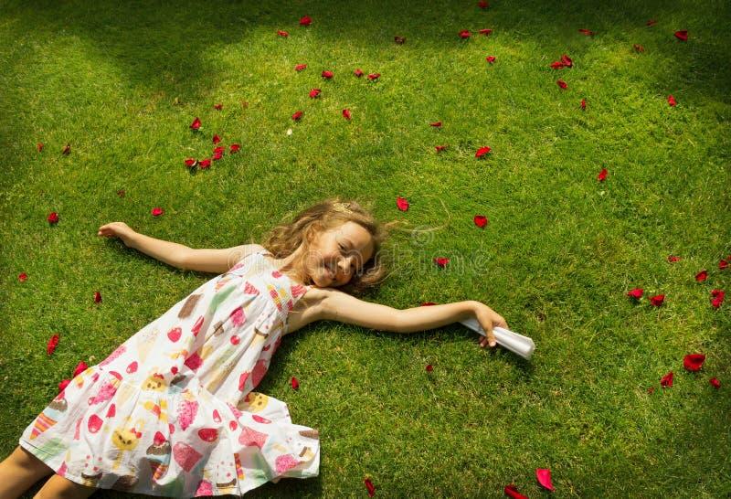 Liten flicka som vilar på ett grönt gräs royaltyfria bilder