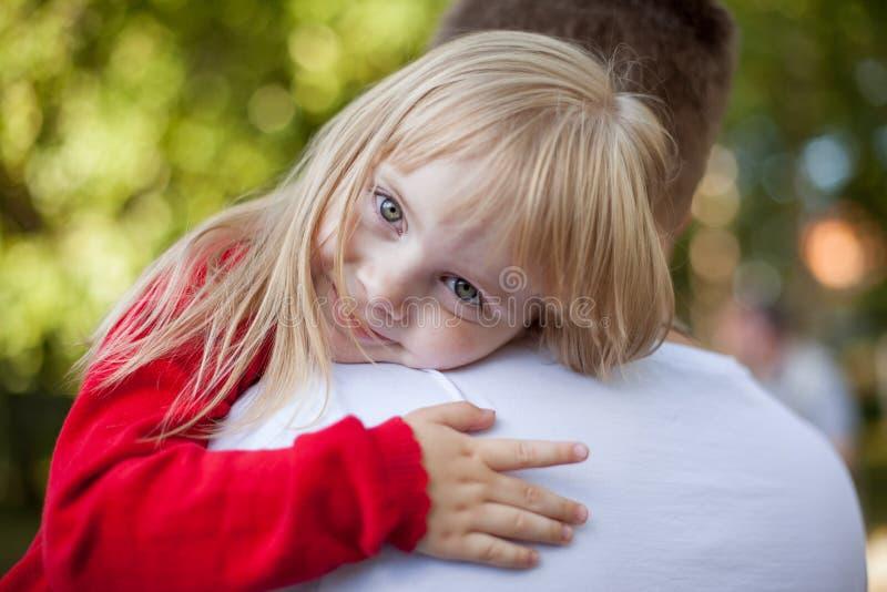 Liten flicka som vilar på hennes faders skuldra royaltyfria foton