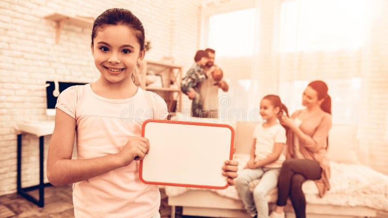 Liten flicka som visar det tomma brädet nära den gulliga familjen arkivbild