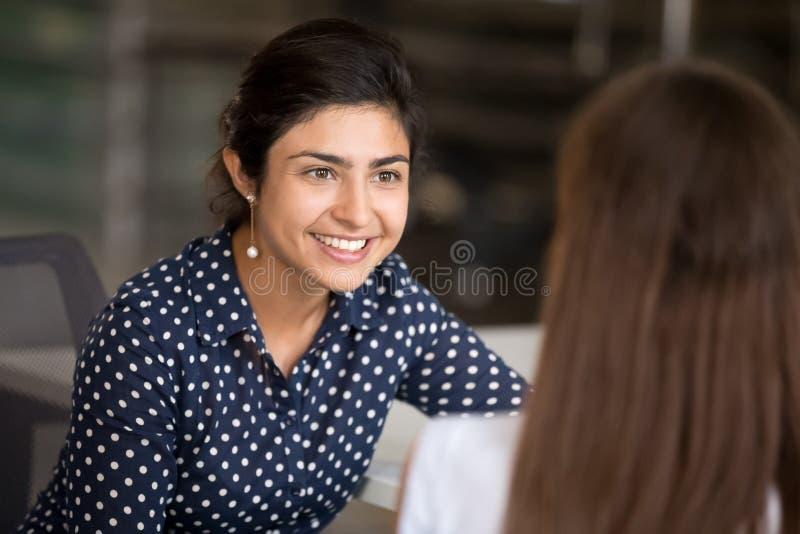 Liten flicka som viskar i det förvånade farmorörat som berättar hemlighet royaltyfri foto