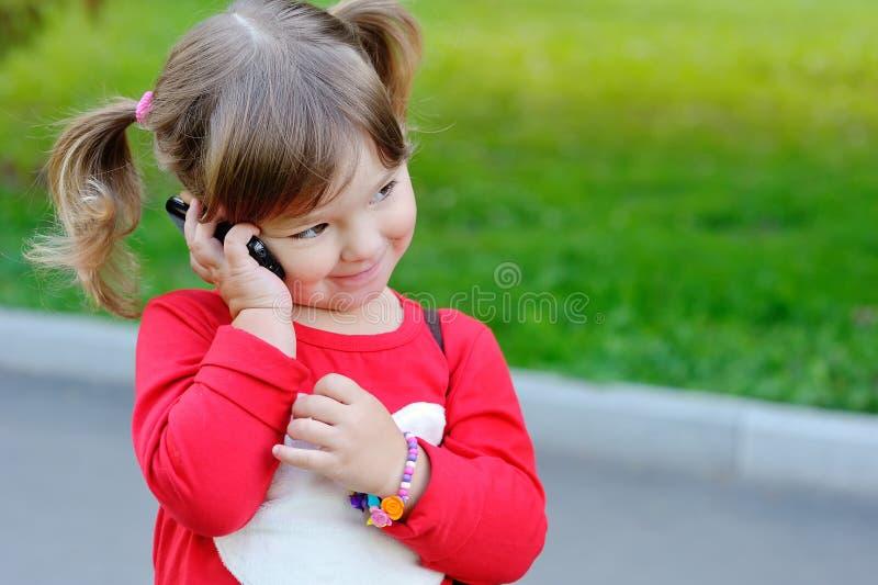 Liten flicka talar ringer by royaltyfria bilder