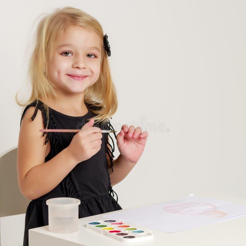 Liten flicka tecknar målarfärger royaltyfria bilder