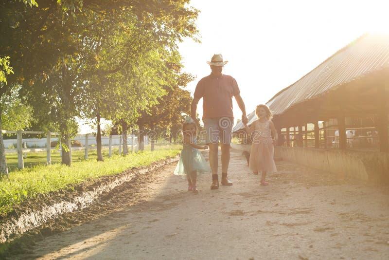 Liten flicka två med farfadern på lantgården royaltyfri bild
