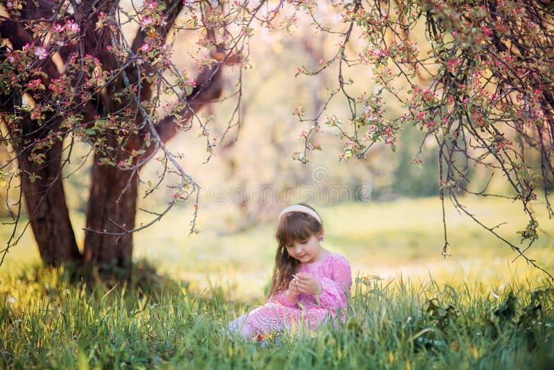 Liten flicka under blommande äppleträd royaltyfri foto