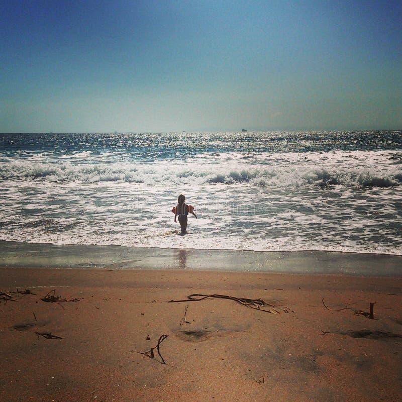 Liten flicka ut i havet med det retro filtret för floaties royaltyfri bild