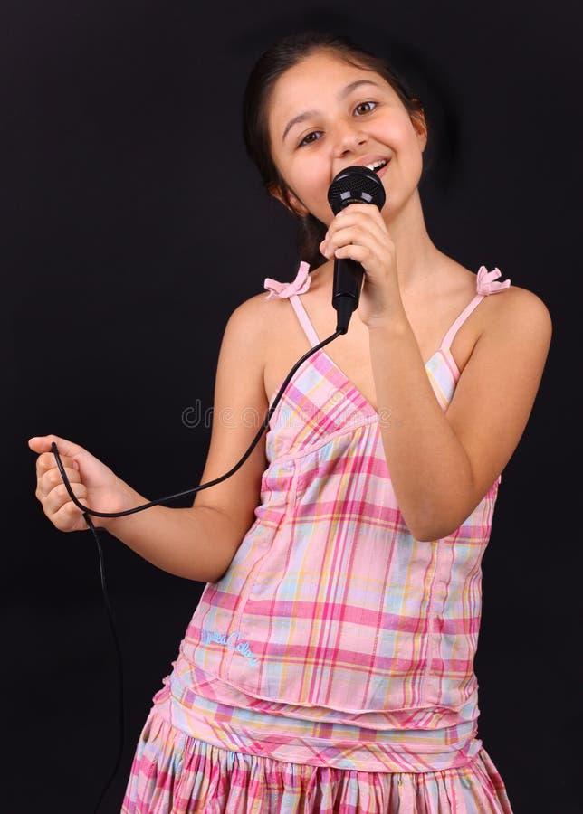 Liten flickaallsånger med mikrofonen arkivfoton