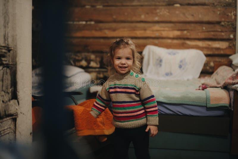 Liten flickaanseende på det gamla trähuset Flickale och blick på kameran royaltyfria foton