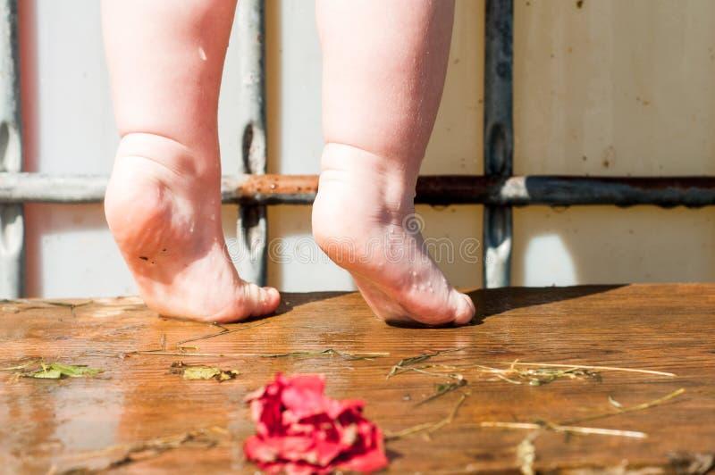 liten flickaanseende som är naket på en stolställning i badrummet hög stol-ställning för vask i badrummet royaltyfri foto