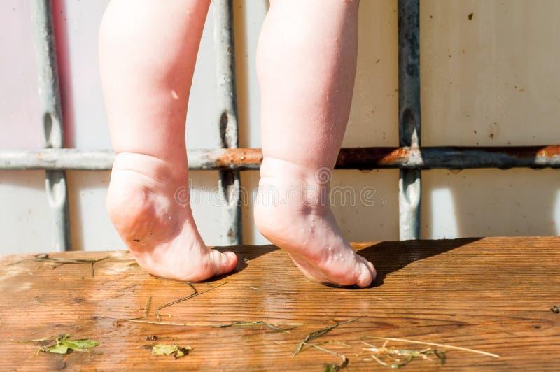 liten flickaanseende som är naket på en stolställning i badrummet hög stol-ställning för vask i badrummet arkivfoto
