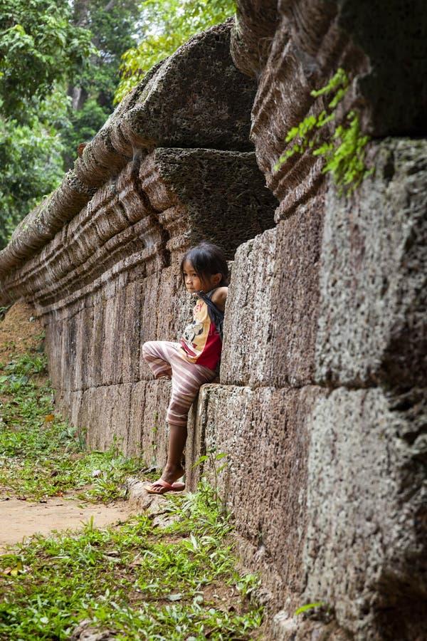 Liten flickaanseendet mot ett gammalt stenar väggen royaltyfri foto