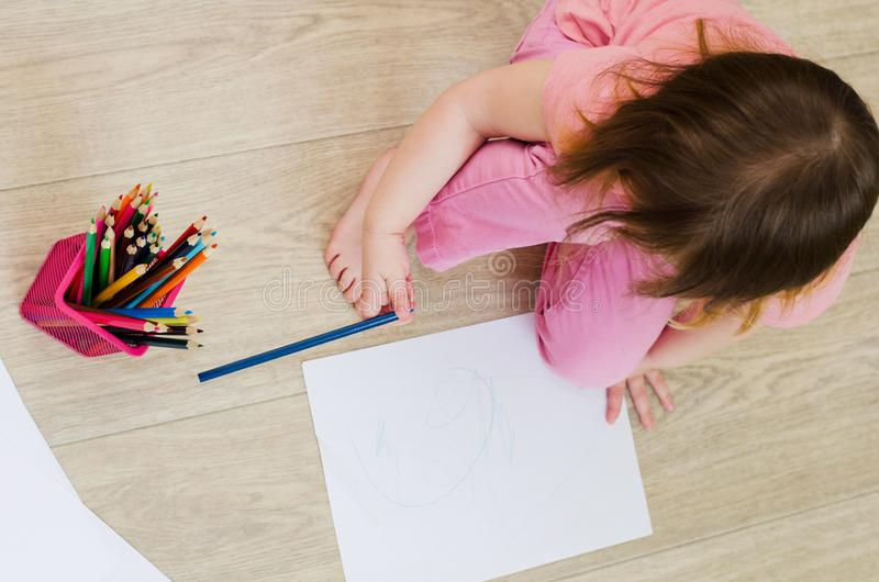 Liten flickaattraktioner med kulöra blyertspennor på golvet arkivfoto