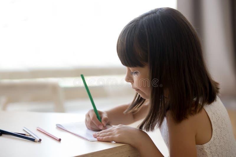 Liten flickaattraktioner på papper som sitter på tabellen arkivfoton