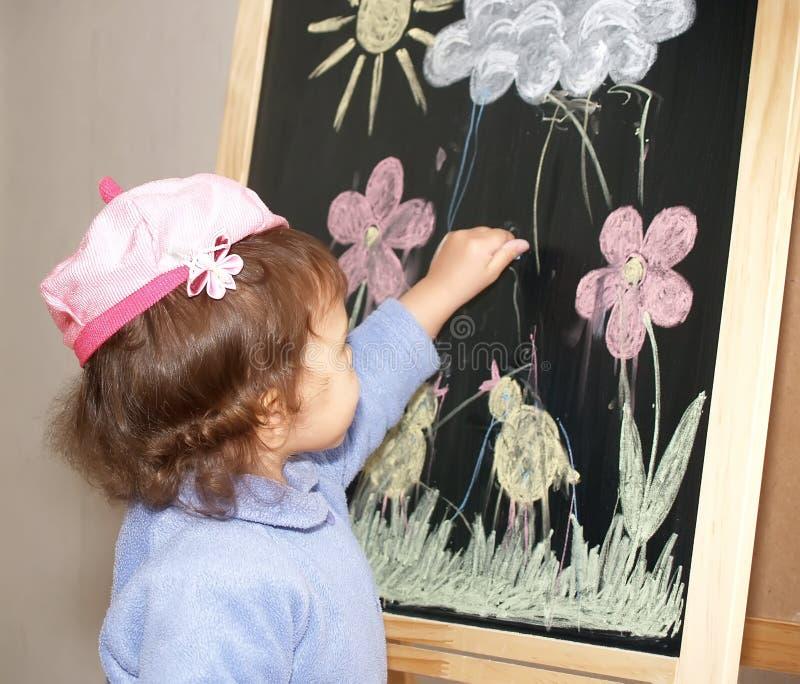 Liten flickaattraktionerna färgar stycken av krita på en staffli arkivfoto
