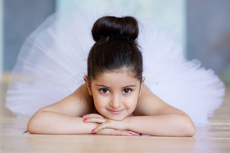 Liten flickaballerina i en vit ballerinakjol arkivfoton