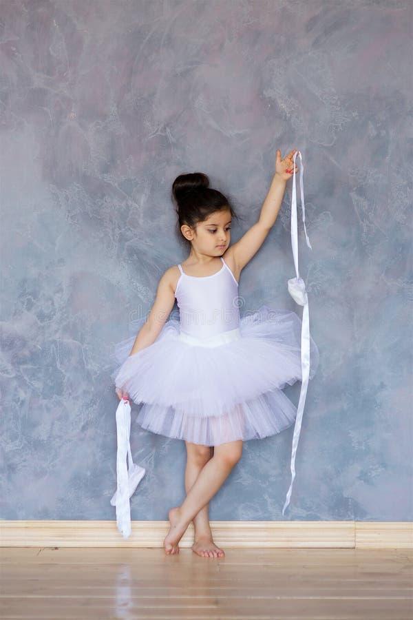 Liten flickaballerina i en vit ballerinakjol arkivbilder