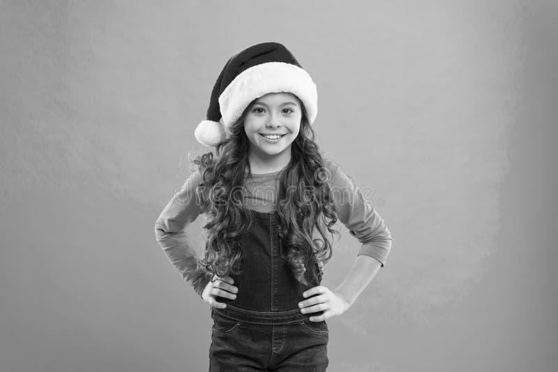 Liten flickabarn i den santa hatten G?va f?r Xmas Barndom Parti f?r nytt ?r Santa Claus unge lycklig ferievinter arkivfoto