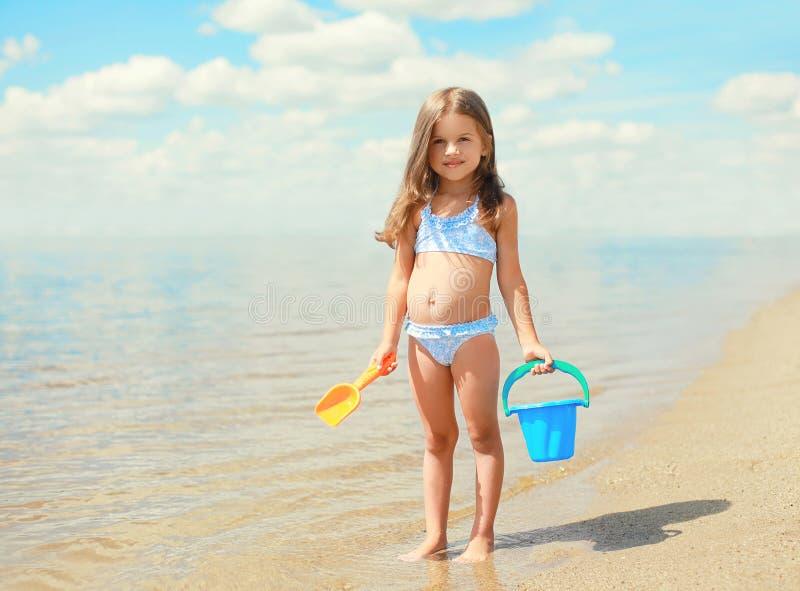 Liten flickabarn med leksaker som spelar och har gyckel på stranden royaltyfri bild