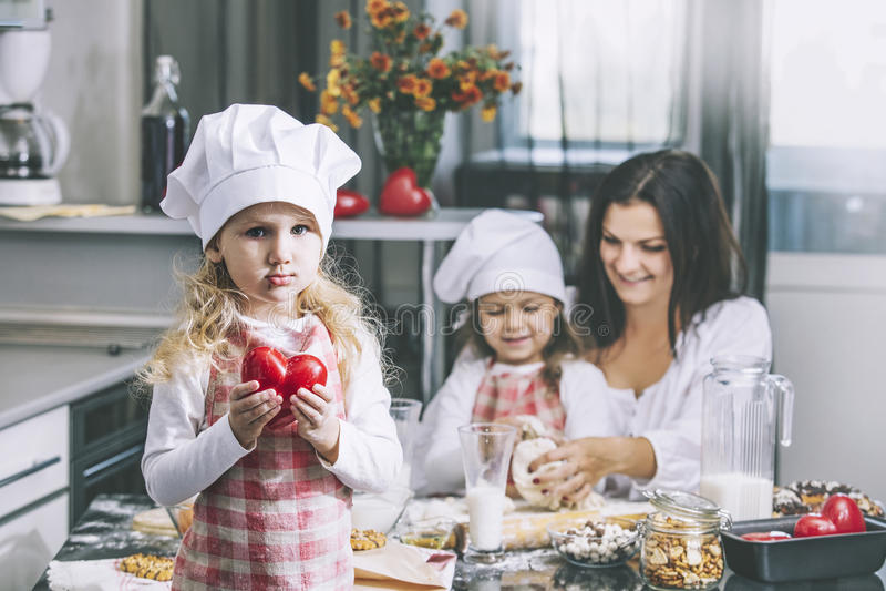 Liten flickabarn med röd hjärta i händer med min mamma och syster royaltyfri foto