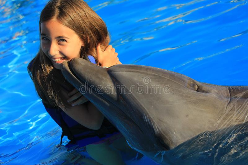 Liten flickabarn som kysser en ursnygg delfinflipper som ler lyckligt ungebad för framsida, buteljerar näsdelfin royaltyfri fotografi