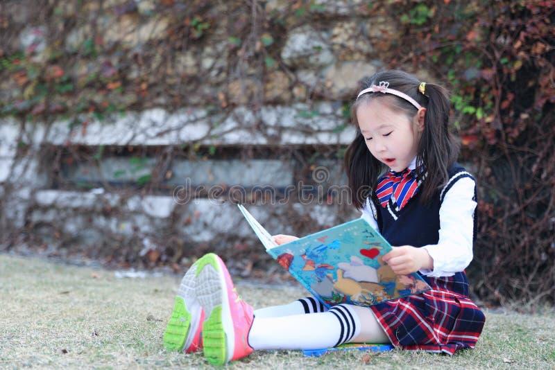 Liten flickabarn som läser en bok på gräset arkivfoto