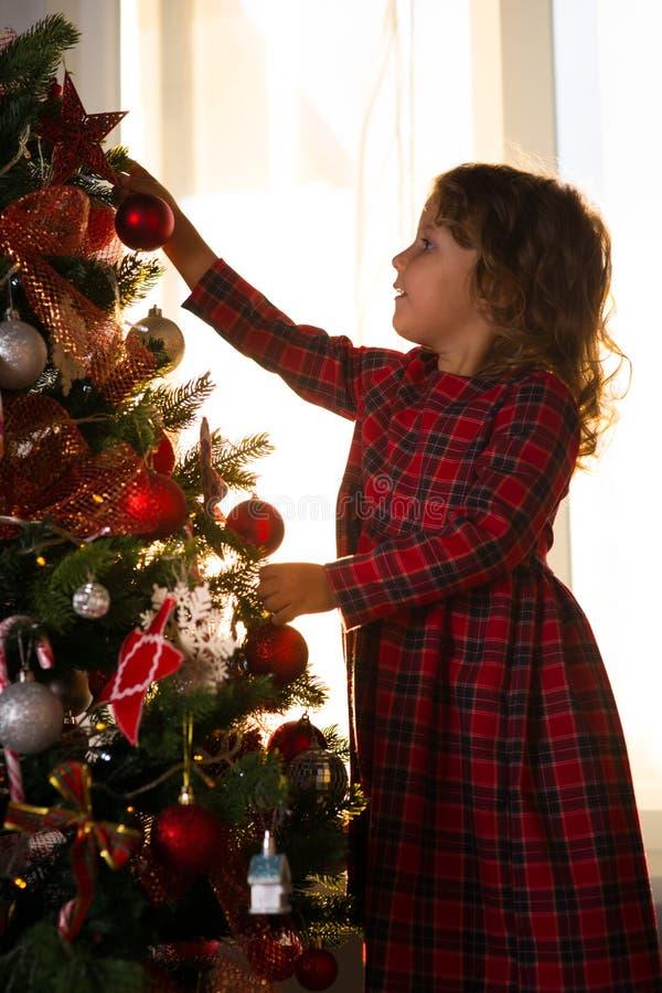 Liten flickabarnet dekorerar en julgran mot fönstret w royaltyfri fotografi