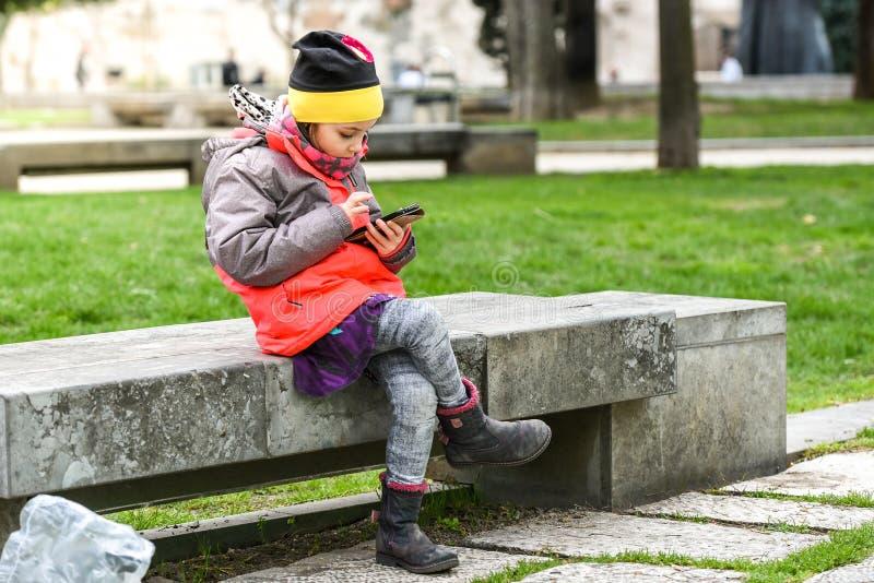 Liten flickabarnet som använder en mobiltelefon parkerar offentligt arkivfoton