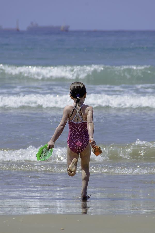 Liten flickabarnspring in till havsvattnet royaltyfri bild
