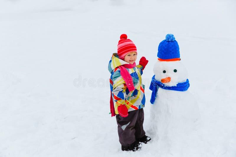 Liten flickabyggnadssnögubbe i vinternatur arkivfoto