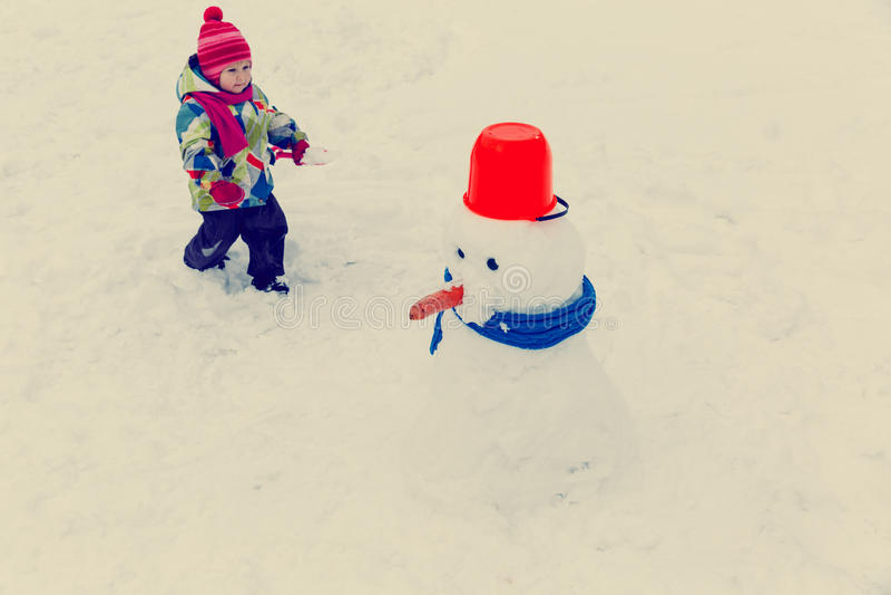 Liten flickabyggnadssnögubbe i vinternatur royaltyfri bild