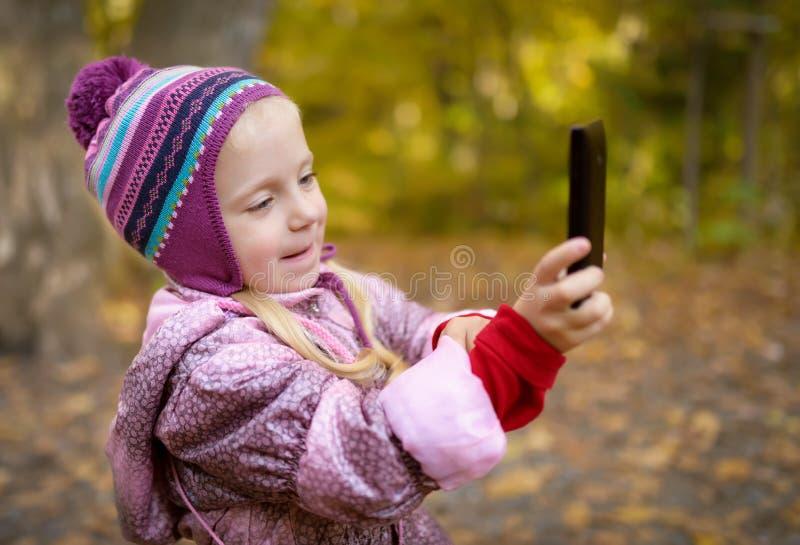 Liten flickadanandefoto eller video med smartphonen royaltyfria foton