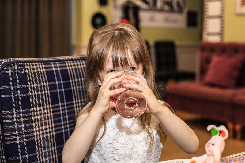 Liten flickadrinkar en dryck royaltyfria foton